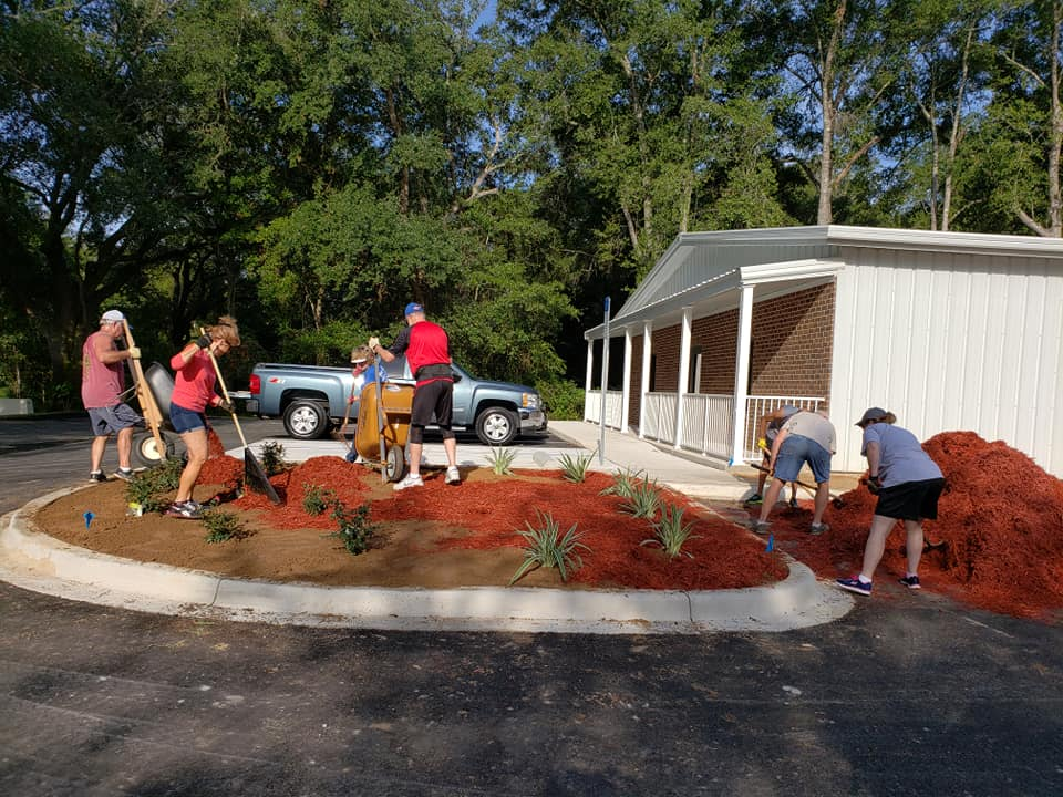 Photo of workers and volunteers landscaping the Santa Rosa Kids House building