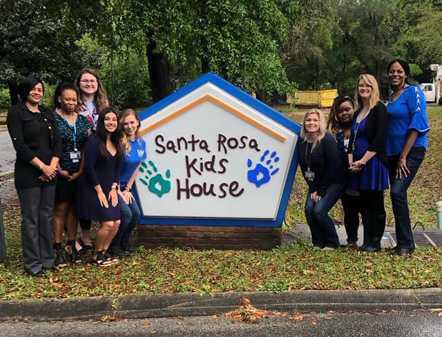 Photo of some members of the Santa Rosa Kids House team posing in front of the organization's sign