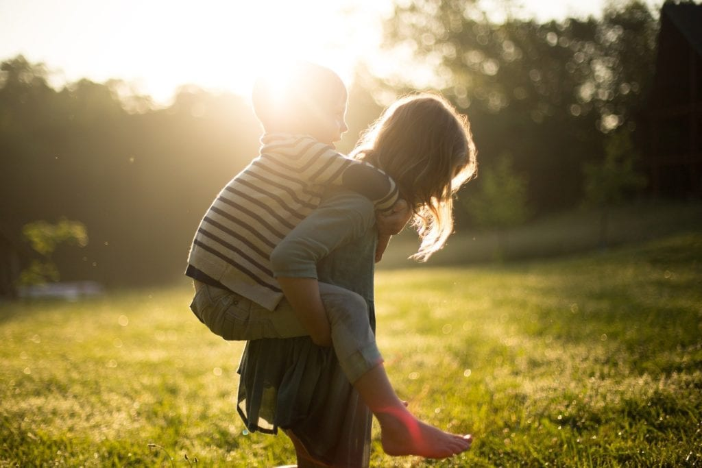 Photo of two young children playing together in a field