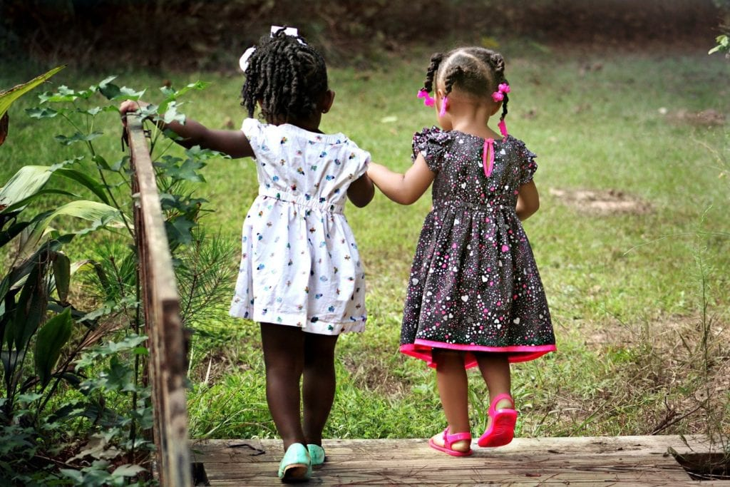 Photo of two young girls playing and holding hands