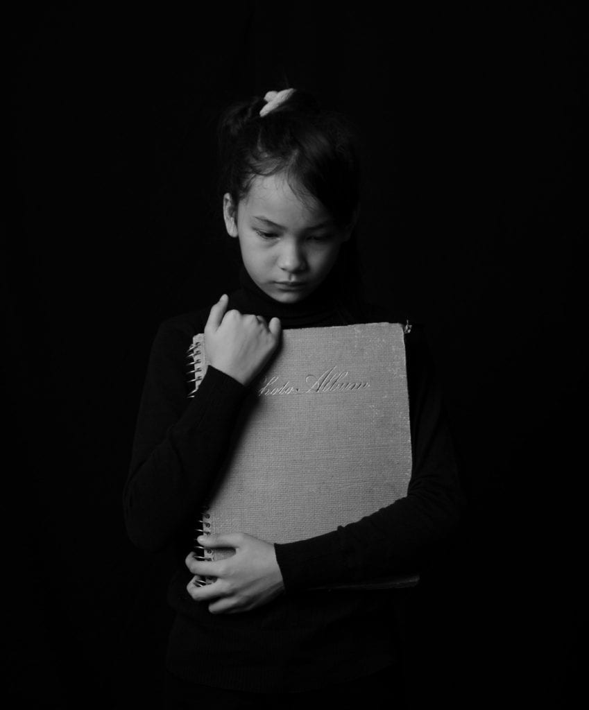 Photo of a young girl looking melancholy and holding a diary